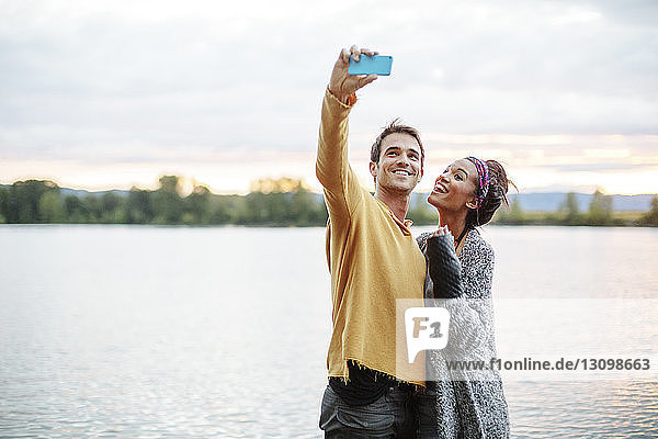 Friends taking selfie while standing by river against sky