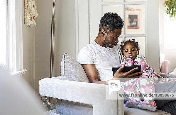 Father showing tablet computer to girl at home