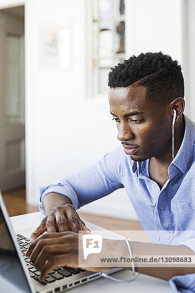 Man listening music while using laptop computer at home