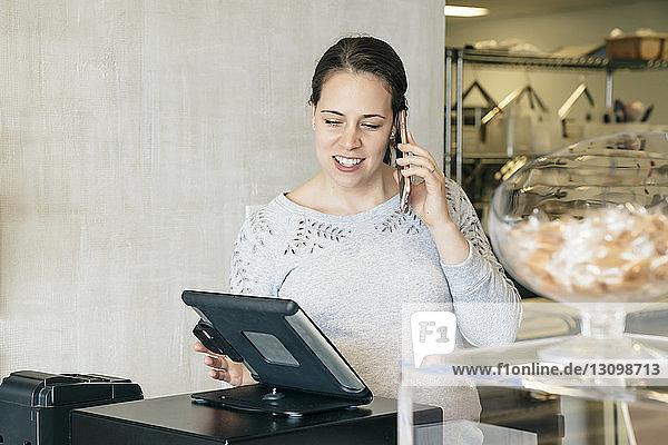 Frau telefoniert mit einem Mobiltelefon  während sie einen Tablet-Computer im Geschäft benutzt