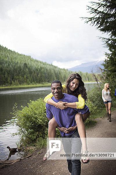 Mann nimmt Frau beim Spaziergang am Flussufer huckepack