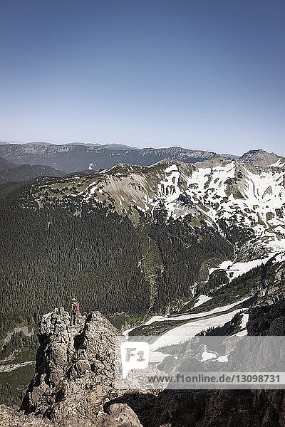 Distant view of hiker standing on mountain