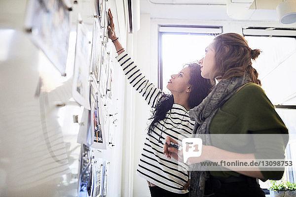Geschäftsfrauen diskutieren über Fotoausdrucke am Schwarzen Brett im Büro