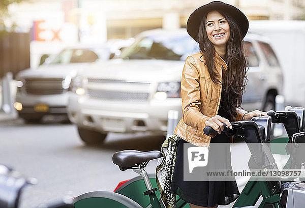 Glückliche Frau mit Hut steht auf Parkplatz