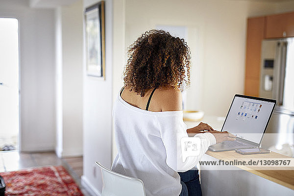Rear view of woman using laptop computer while sitting at home