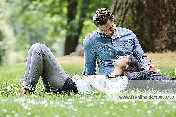 Glückliche Freundin liegt im Park auf dem Schoß ihres Freundes