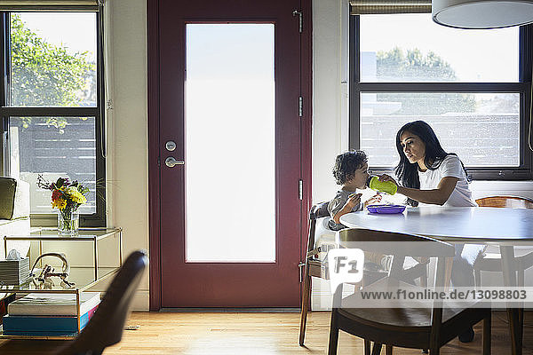Mother feeding water to son from bottle while sitting against window at home