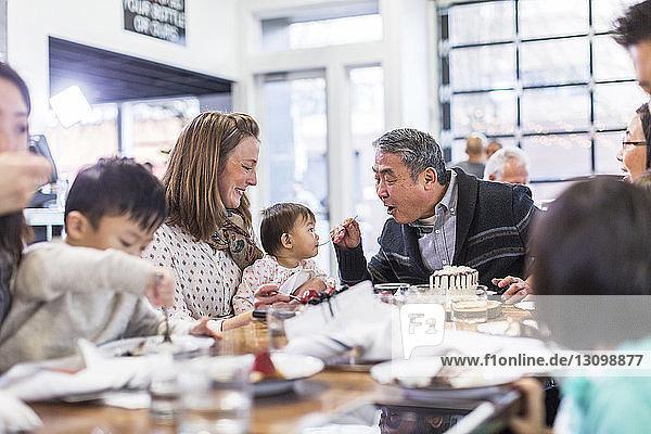 Großvater füttert ein kleines Mädchen mit Kuchen  während er mit der Familie im Restaurant sitzt