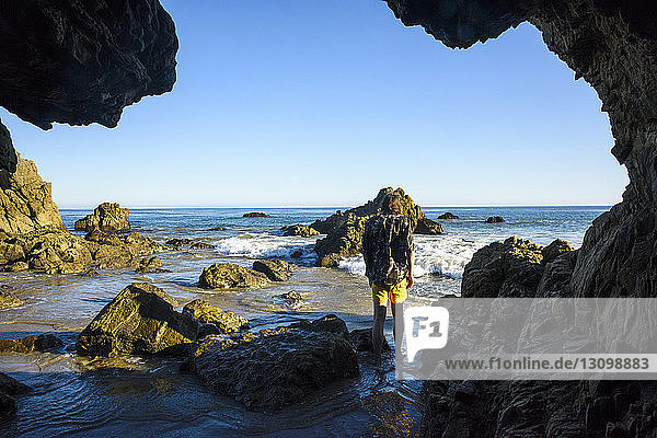 Rear view of man standing at shore against clear sky seen through cave