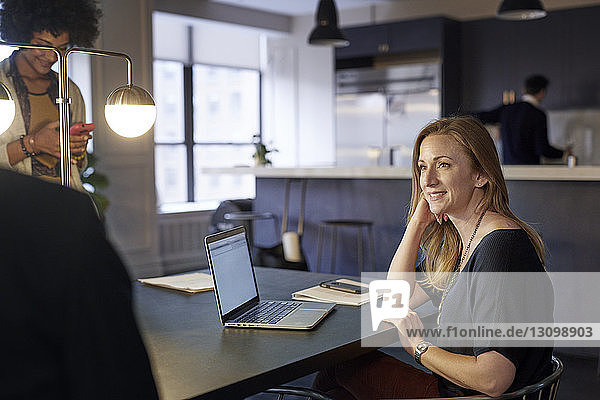 Happy businesswoman looking away while female colleague using smart phone in creative office