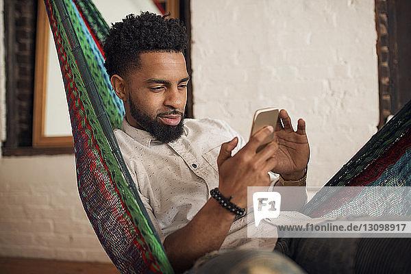 Mann benutzt Smartphone  während er zu Hause auf der Hängematte sitzt