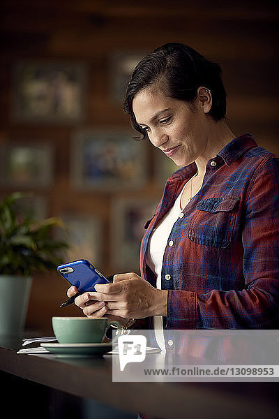 Smiling woman with coffee on table using mobile phone in cafe
