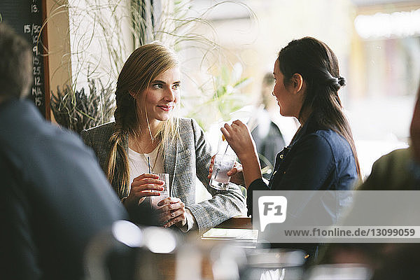 Female friends talking while having drinks by window in restaurant
