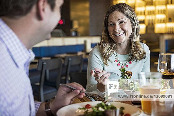 Glückliches Paar unterhält sich beim Salatessen im Restaurant