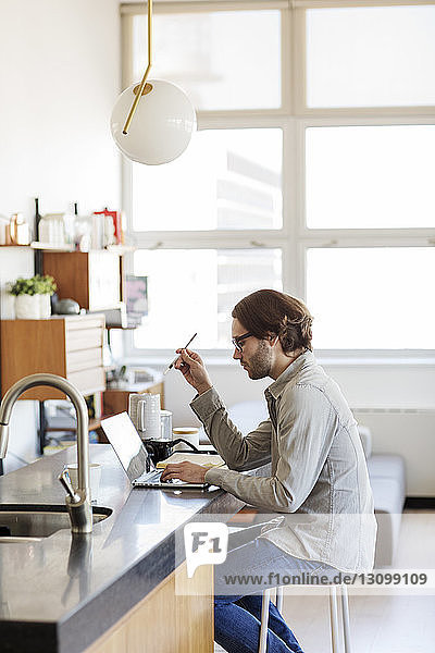 Side view of man using laptop computer on kitchen island at home