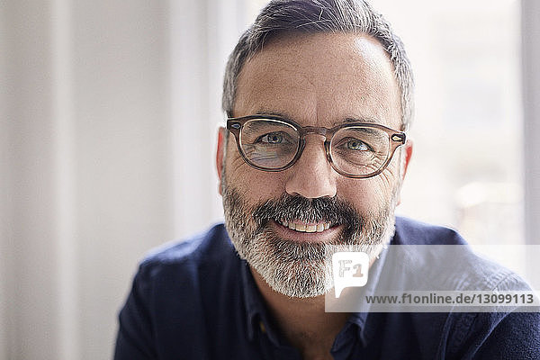 Porträt eines lächelnden Geschäftsmannes  der im Kreativbüro sitzt