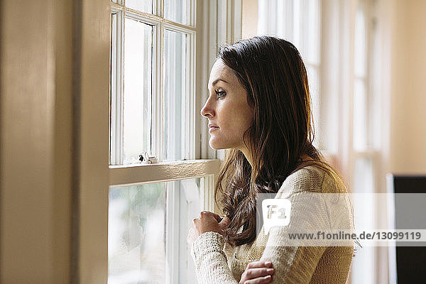 Side view of thoughtful woman standing by window at home