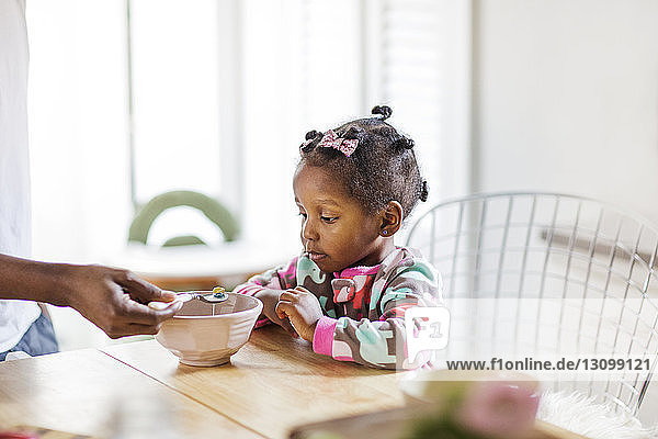 Midsection of father feeding breakfast cereals to daughter at home
