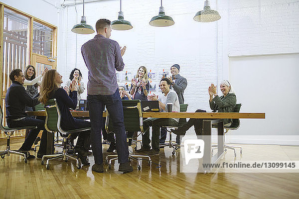 Business people applauding in board room at office
