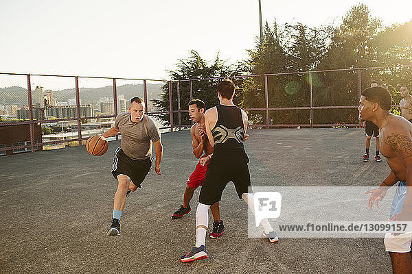Friends playing basketball in court