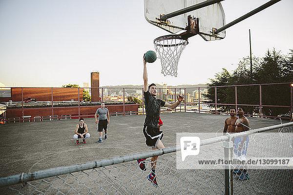 Freunde beobachten  wie ein Mann beim Üben von Basketball vor Gericht eintaucht