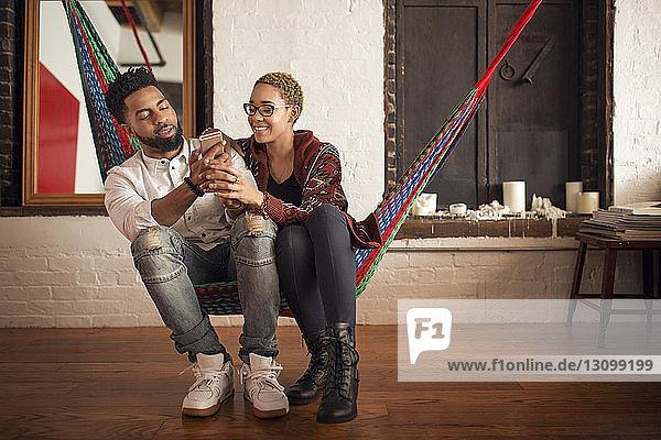 Junges Paar benutzt Smartphone  während es zu Hause auf der Hängematte sitzt