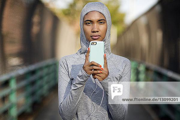 Porträt einer Frau mit Kapuzenhemd bei der Benutzung eines Smartphones auf einem Fußweg