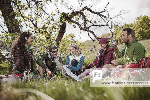 Happy hikers looking at map while sitting on grassy field
