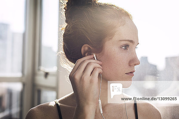 Close-up of thoughtful woman listening music at home