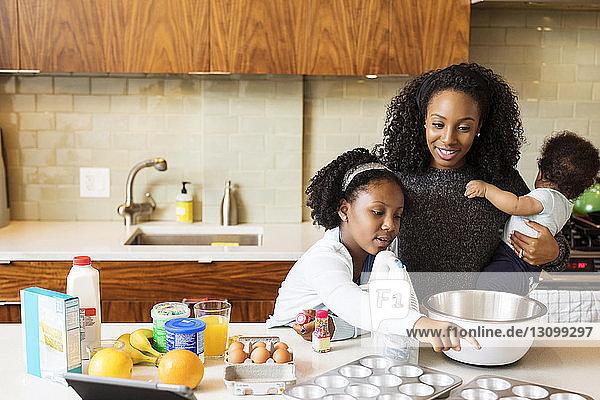 Mutter mit Sohn sieht Tochter beim Backen von Cupcakes in der Küche