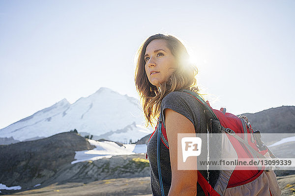 Woman with backpack looking away while standing against clear sky during sunny day
