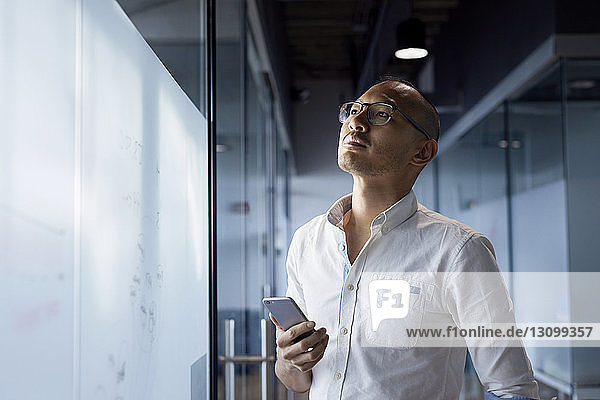 Thoughtful businessman holding smart phone while standing by glass wall at office
