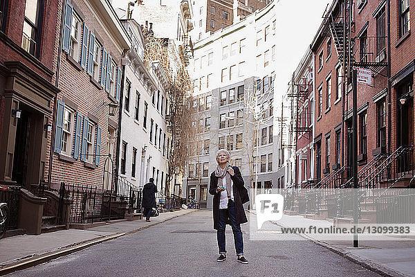 Ältere Frau in voller Länge auf Stadtstraße stehend
