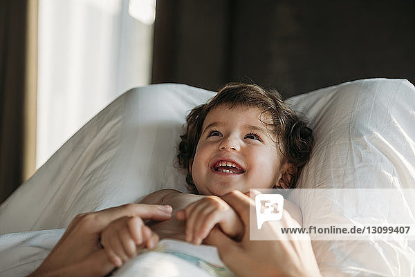 Midsection of mother playing with cheerful daughter at home
