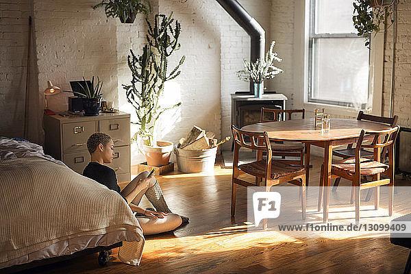 Frau benutzt Smartphone  während sie im Schlafzimmer auf dem Boden sitzt