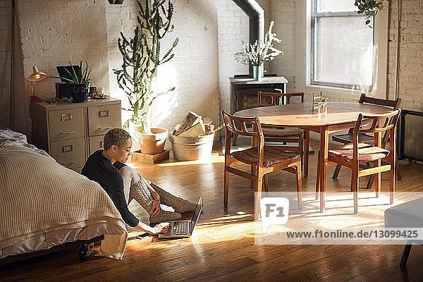 Seitenansicht einer Frau  die einen Laptop benutzt  während sie im Schlafzimmer auf dem Boden sitzt