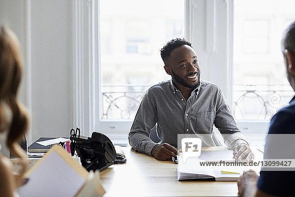 Lächelnder Geschäftsmann im Gespräch mit einem Kollegen am Schreibtisch gegen ein Fenster im Büro