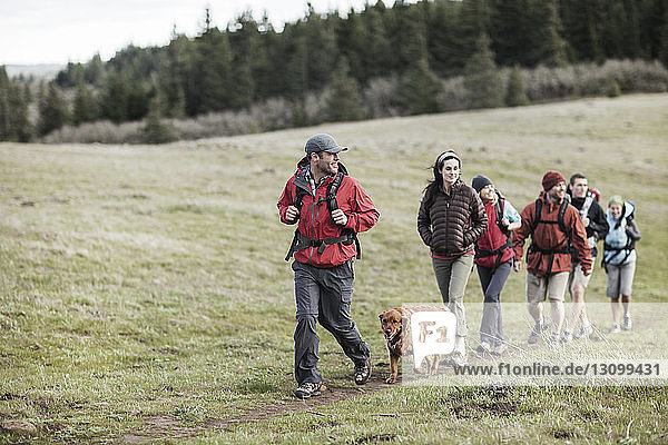 Friends with dog hiking on field