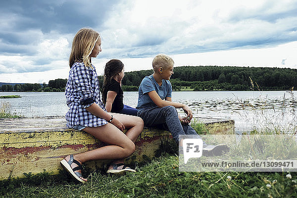 Siblings looking at view while sitting on retaining wall at lakeshore against stormy clouds