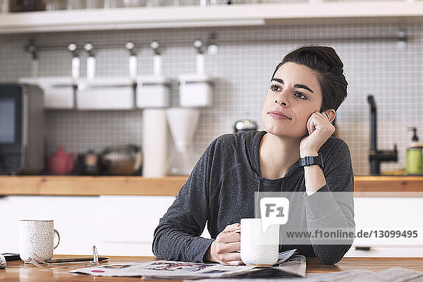 Woman with newspapers and coffee cup looking away while sitting at dining table