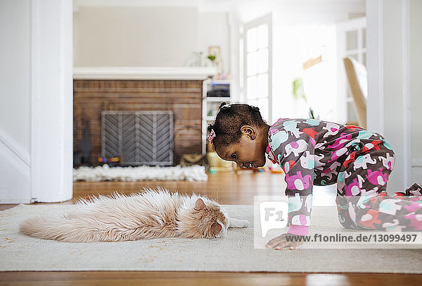 Side view of curious girl looking at cat lying on rug in living room