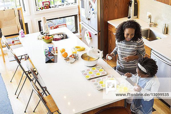 Hochwinkelansicht der Mutter mit Tochter beim Anordnen von Cupcake-Haltern in Tabletts