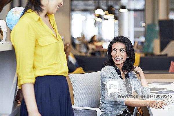 Glückliche Geschäftsfrau betrachtet Kollegin bei der Arbeit im Büro