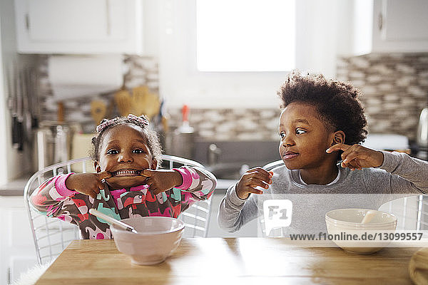 Portrait of playful girl making face while brother looking at her in kitchen