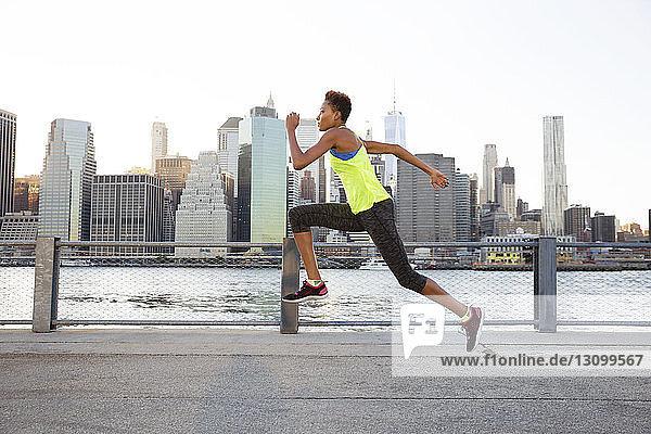 Athlet springt auf Promenade am Fluss gegen klaren Himmel