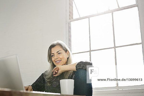 Smiling woman using laptop at table against window at home