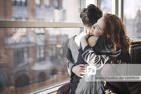 Lesbian couple embracing while sitting on window sill at home