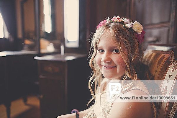 Portrait of smiling flower girl sitting on chair at home