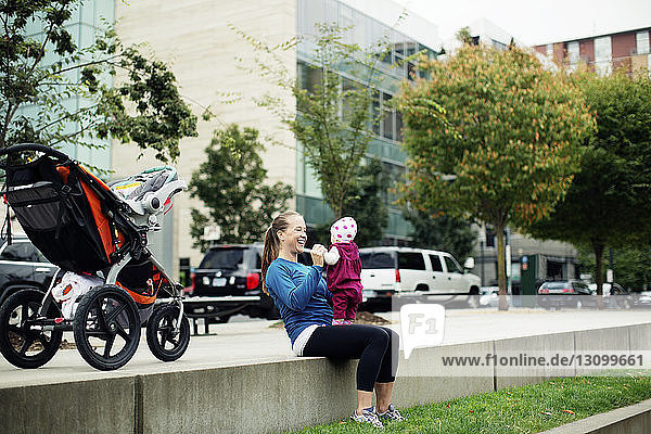 Cheerful mother playing with baby girl while sitting on retaining wall in city