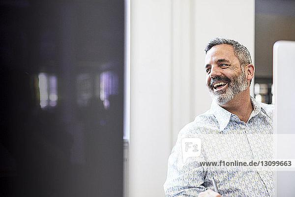 Fröhlicher Geschäftsmann schaut bei der Arbeit im Büro weg